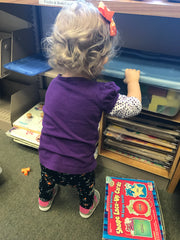 toddler girl looking at books on a shelf in the library