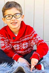 little boy with glasses smiling wearing his holiday sweater