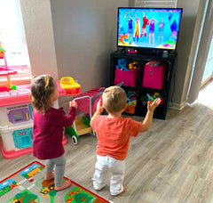 twin boy and girl toddler dancing to a kids tv program