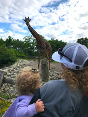 mom and daughter looking at a giraffe