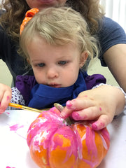 toddler girl painting a pumpkin at the library
