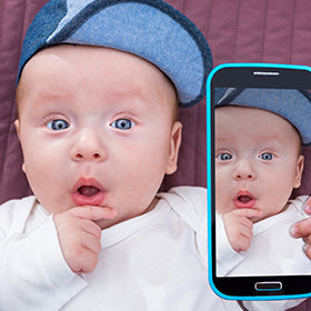 A baby taking a selfie with their parent's phone as a brand ambassador for bblittles