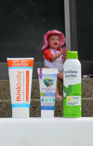Sunscreen bottles with a baby in the background
