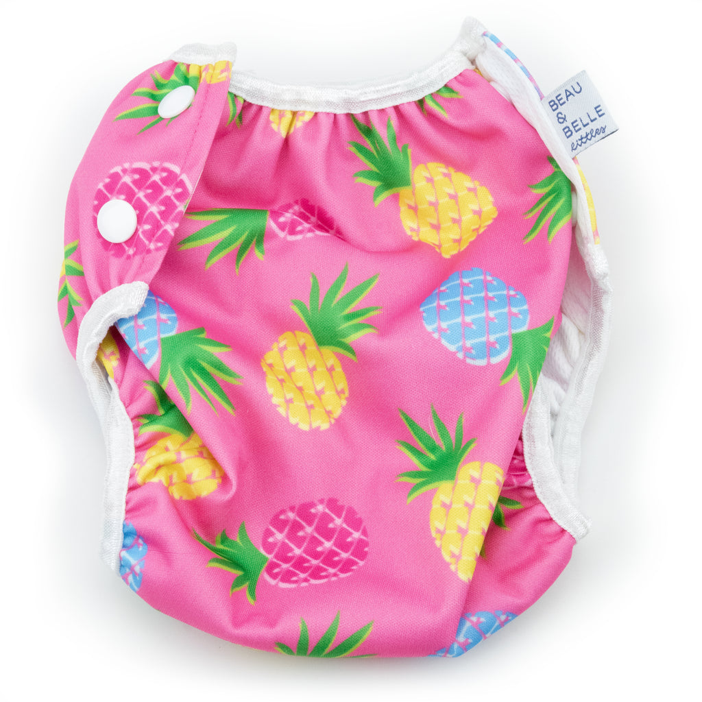Beau and Belle Littles Swim Diaper, Regular Size, light pink background with yellow, dark pink, and blue pineapples, flat lay, back view