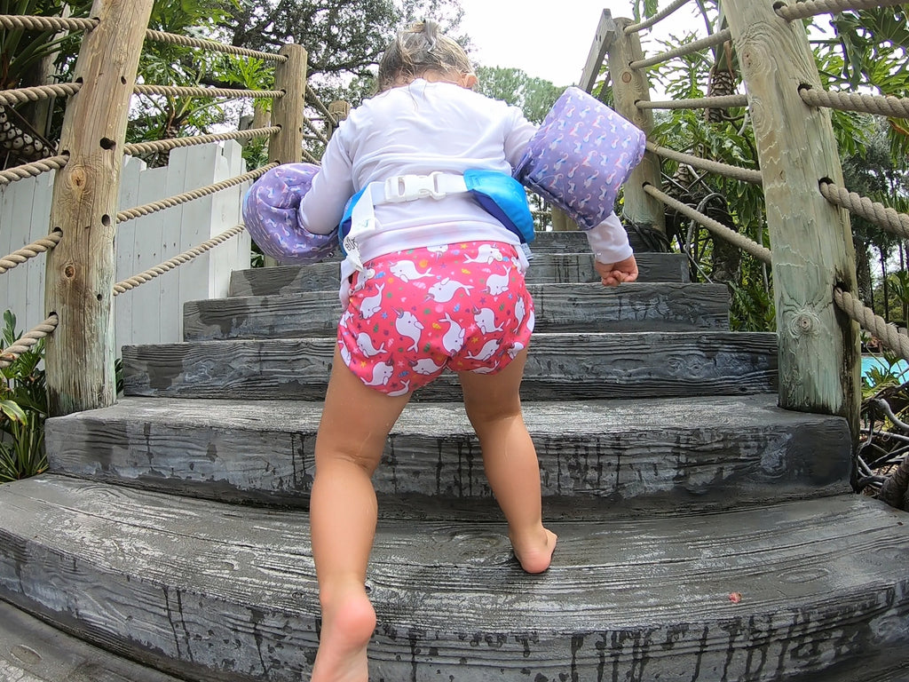 toddler walking up stairs wearing a Beau and Belle Littles Swim Diaper, Larger Size, dark pink background, narwhals