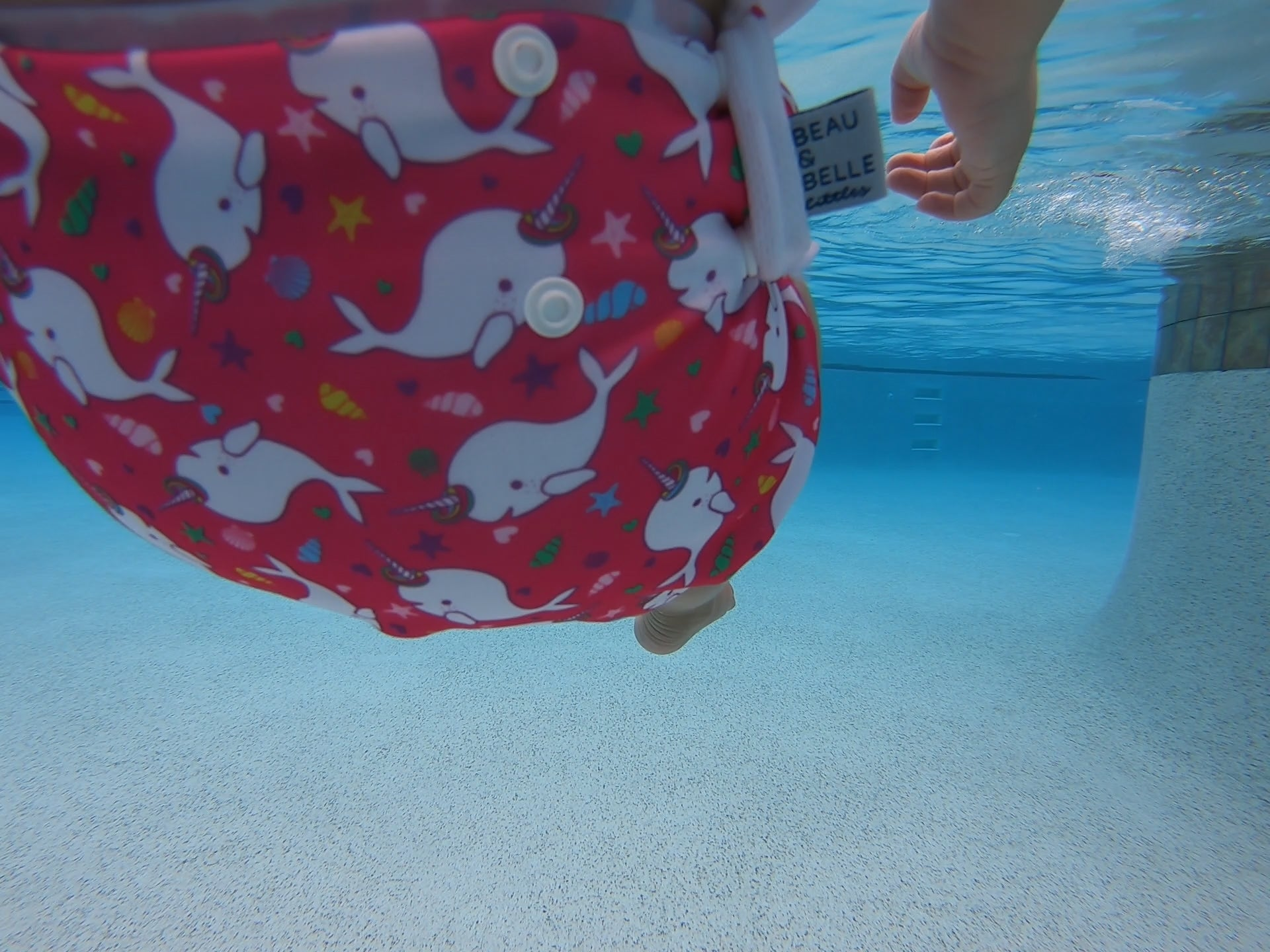underwater image of a Beau and Belle Littles Swim Diaper, Larger Size, dark pink background, narwhals