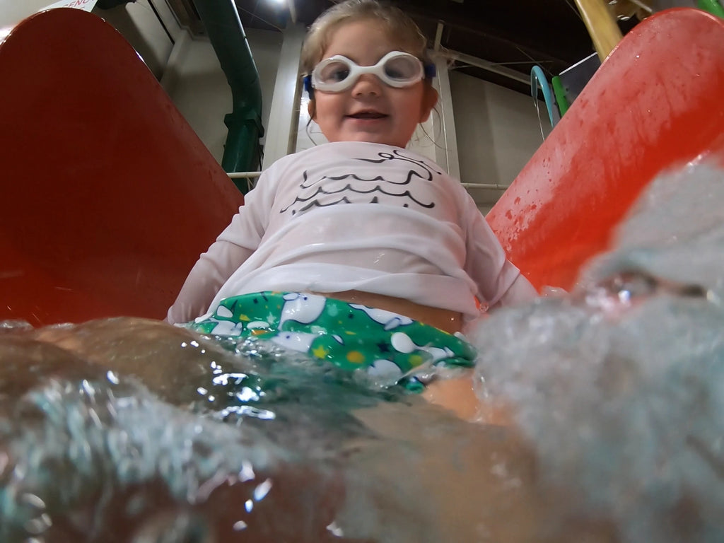 toddler girl at the bottom of a water slide wearing a Beau and Belle Littles Swim Diaper, Regular Size, green background, narwhals