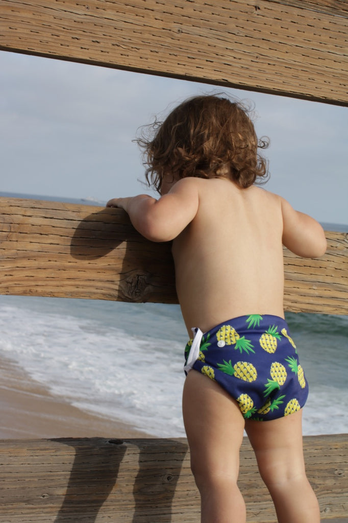 baby at the beach wearing Beau and Belle Littles Swim Diaper, Regular Size, Navy blue with pineapples