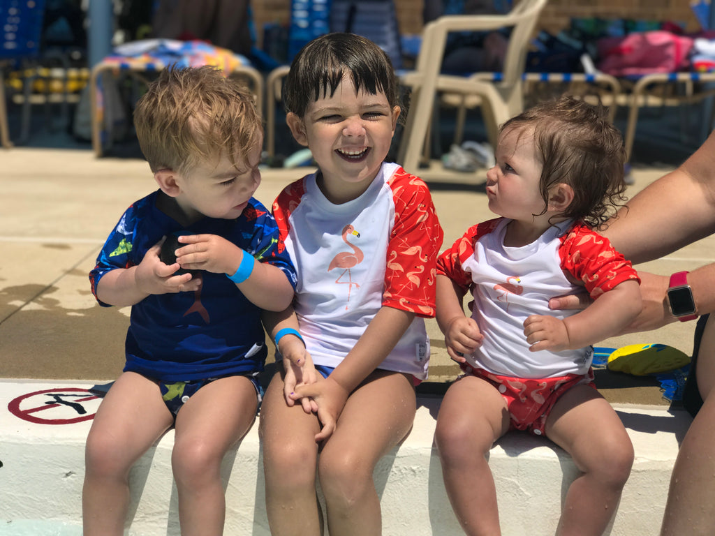 three children sitting on the edge of the pool - two girls wearing the Beau and Belle Littles Rash Guard/Swim Shirt, white with pink 3/4 sleeves, flamingo print, one boy wearing  a Beau and Belle Littles Rash Guard/Swim Shirt, dark blue with lighter blue 3/4 sleeves, shark print