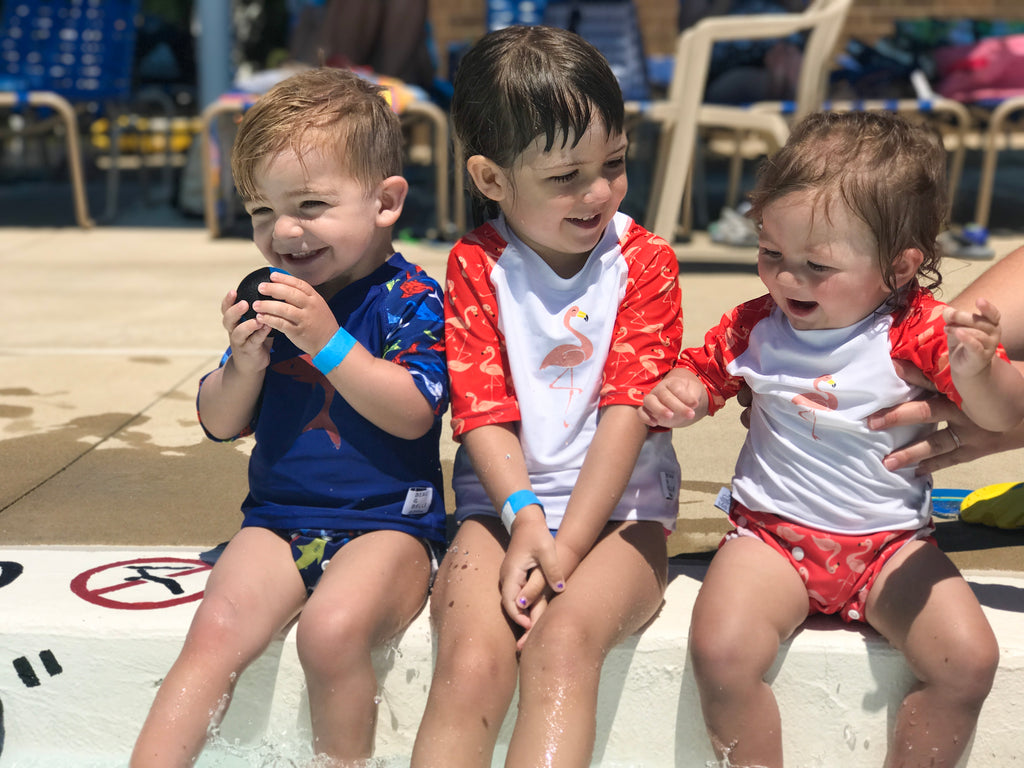 three children laughing and sitting on the edge of the pool - two girls wearing the Beau and Belle Littles Rash Guard/Swim Shirt, white with pink 3/4 sleeves, flamingo print, one boy wearing a Beau and Belle Littles Rash Guard/Swim Shirt, dark blue with lighter blue 3/4 sleeves, shark print