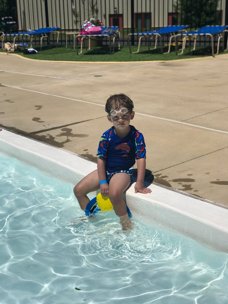 boy sitting on the edge of a pool wearing a Beau and Belle Littles Rash Guard/Swim Shirt, dark blue with lighter blue 3/4 sleeves, shark print and matching swim diaper