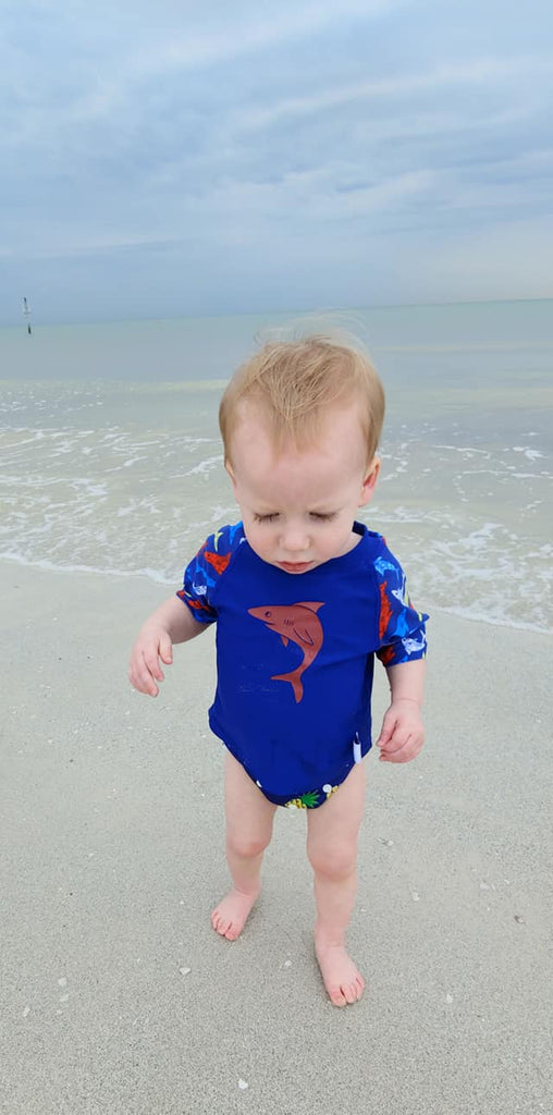 baby boy wearing a Beau and Belle Littles Rash Guard/Swim Shirt, dark blue with lighter blue 3/4 sleeves, shark print