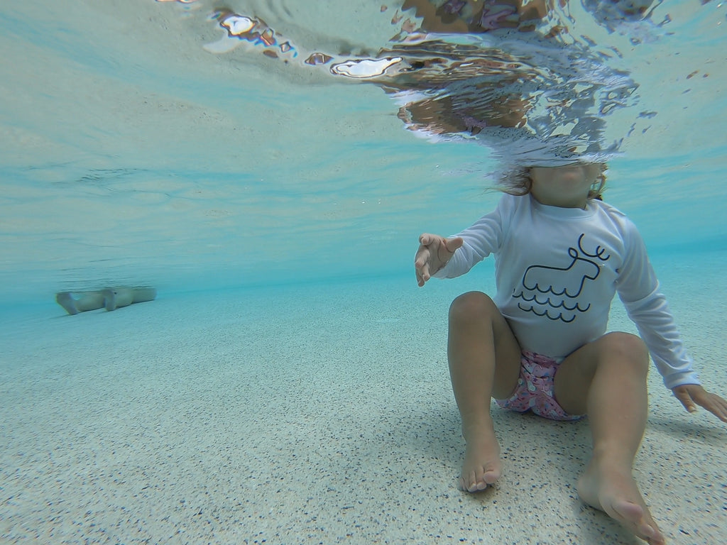underwater image of a toddler wearing a Beau and Belle Littles Swim Diaper, Regular Size, light pink background, narwhals