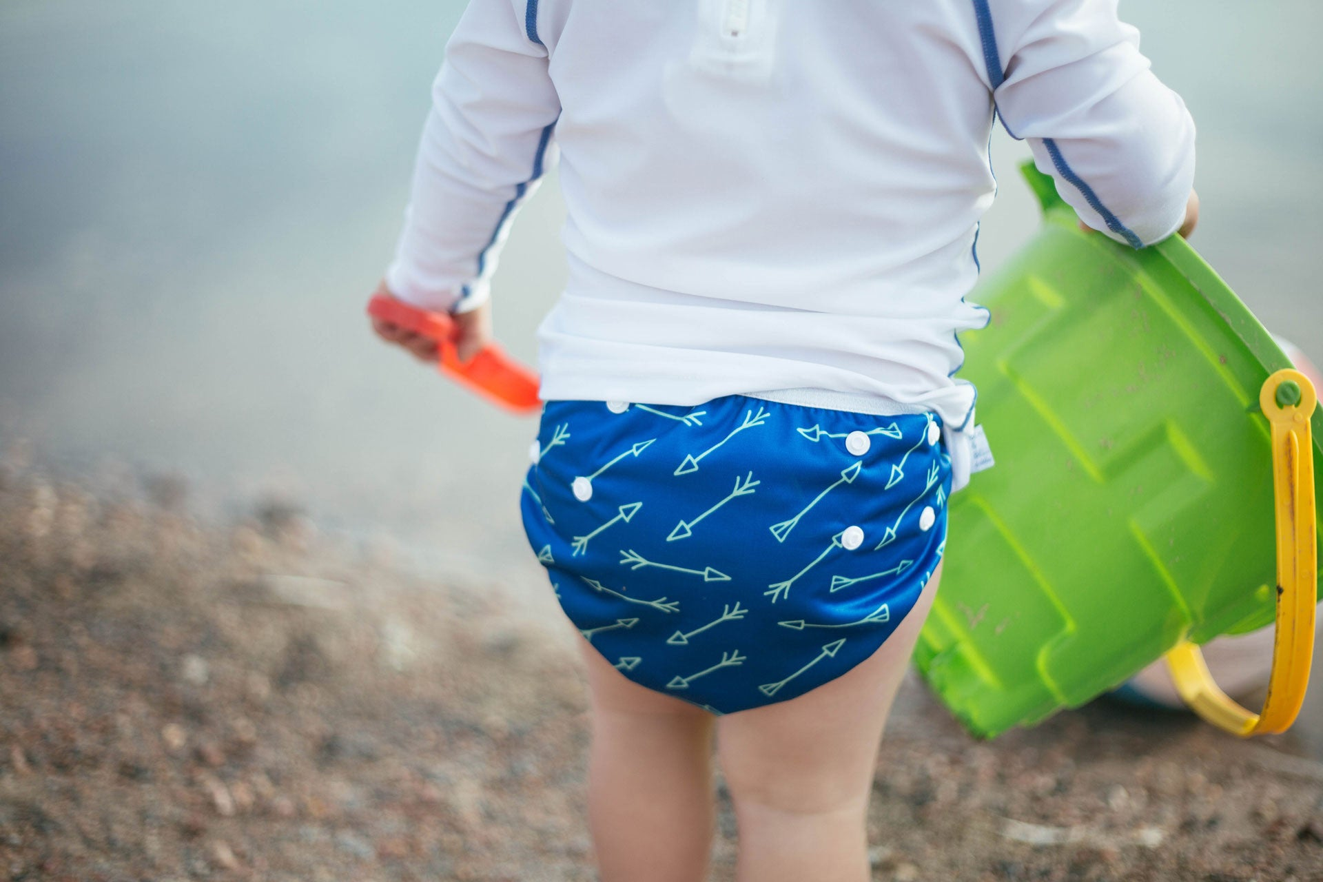 image of child at the beach wearing a Beau and Belle Littles Swim Diaper, Regular Size, blue with green arrows