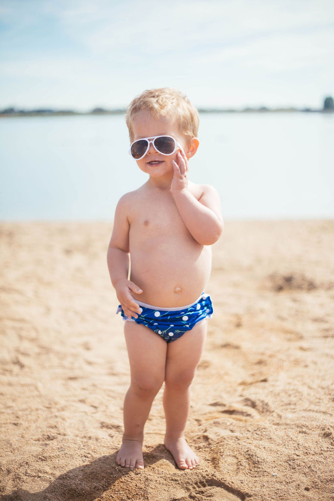 boy on the beach wearing sunglasses and a Beau and Belle Littles Swim Diaper, Regular Size, blue with green arrows