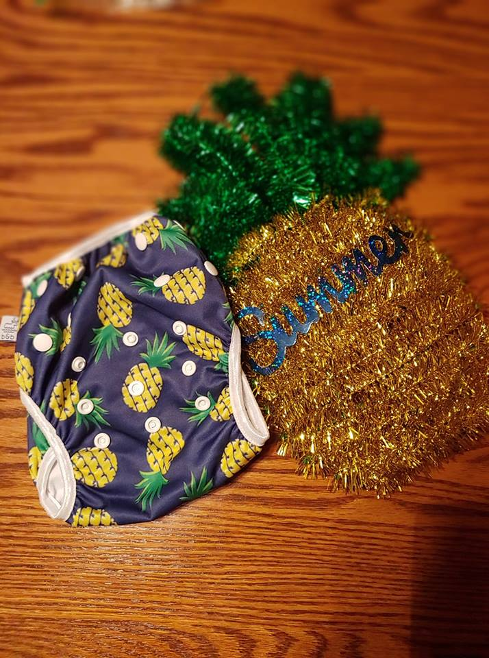 "Beau and Belle Littles Swim Diaper, Regular Size, Navy blue with pineapples next to a pineapple prop that says ""summer"""