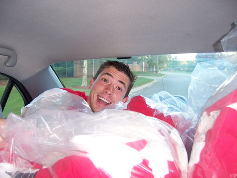 greg on a pile of t-shirts in the back seat of a car