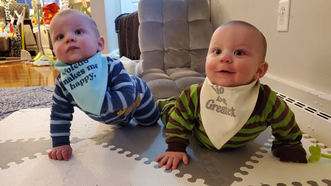 twin babies on the floor wearing bibs, one saying toledo makes me happy, the other says ohio is the greatest