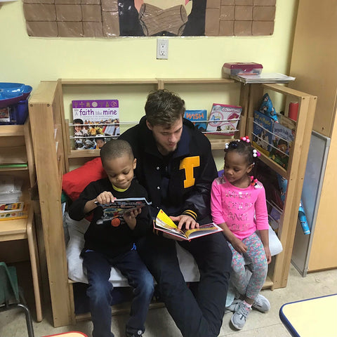 Bailey Flint reading a book to kids at My First Days Daycare
