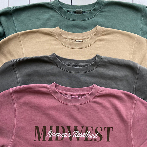 pigment dyed crew sweatshirts stacked with the sweatshirt on the top reading midwest america's heartland
