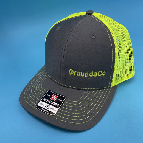 embroidered trucker hat with gray front and bill and neon yellow mesh with grounds co logo on left panel