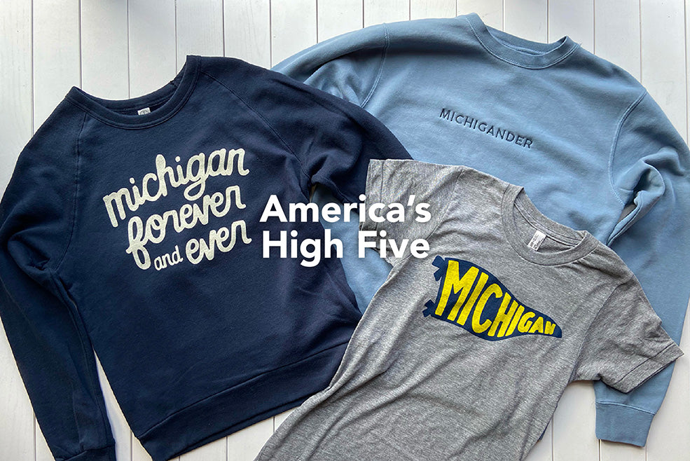 """America's High Five"" atop a navy blue Michigan Forever and Ever sweatshirt, a blue tone-on-tone Michigander embroidered sweatshirt and a gray short sleeved t-shirt with a navy blue pennant design with ""Michigan"" in yellow ink."
