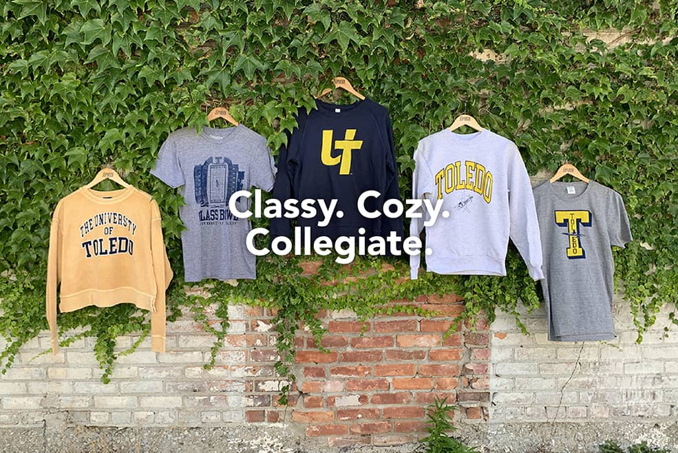 """Classy. Cozy. Collegiate"" text atop an image of an assortment of unisex and Women's University of Toledo apparel, including sweatshirts and t-shirts."
