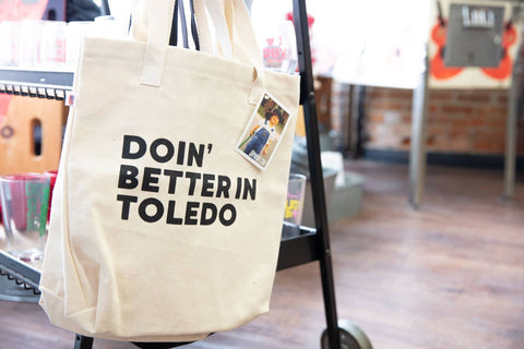 tote bag that has the words doin' better in toledo screen printed on it