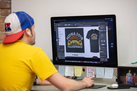 graphic designer creating a design on a computer for screen printing on a t-shirt