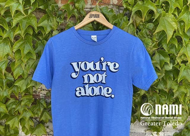 "NAMI of Greater Toledo Community Shirt: Short sleeved blue shirt with ""you're not alone."" in white text with a navy outline."