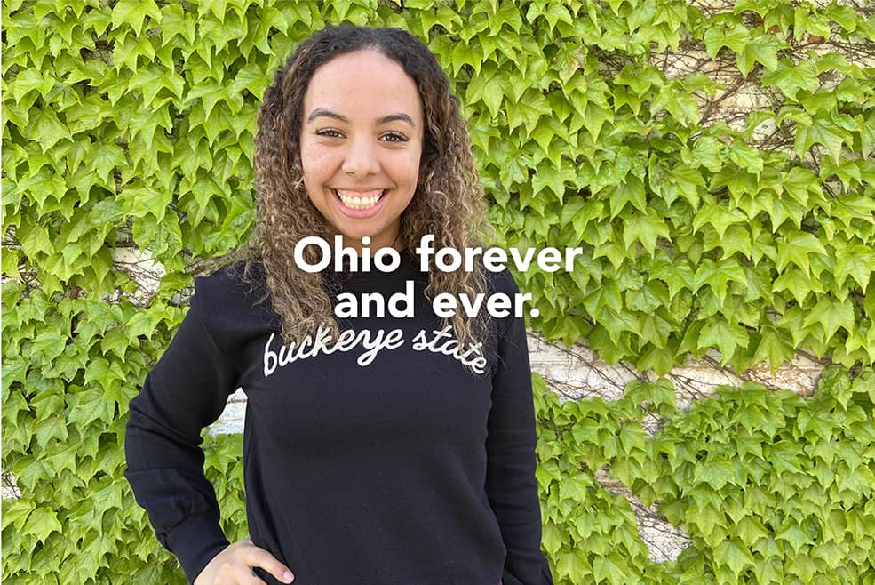 "Ohio forever and ever. Image: Woman in a black sweatshirt with ""buckeye state"" in cream ink in cursive arched across chest."