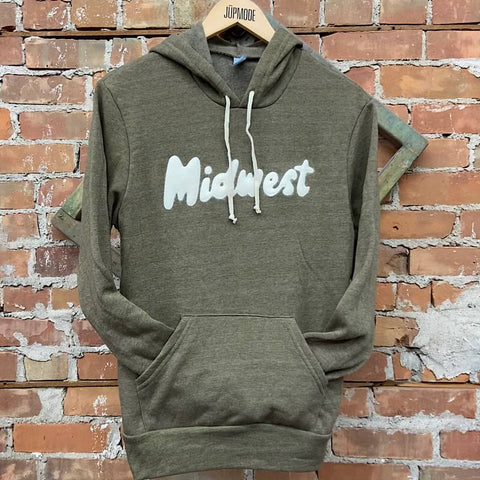 midwest hoodie on a hanger against a brick wall