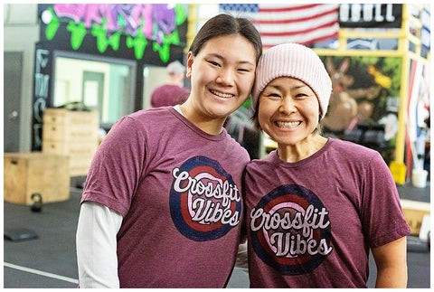 two women smiling in a crossfit gym while wearing matching shirts that say crossfit vibes