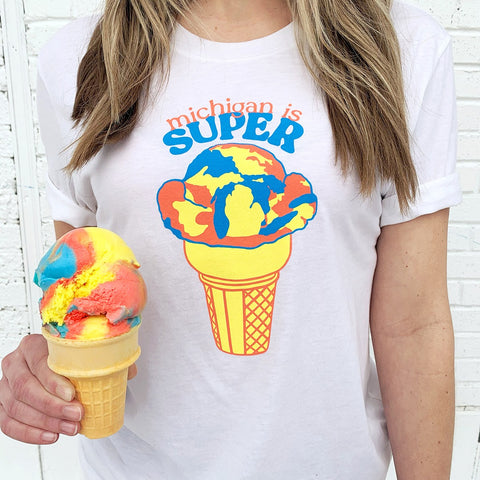 woman wearing a michigan is super shirt with an ice cream cone on it while holding an ice cream cone