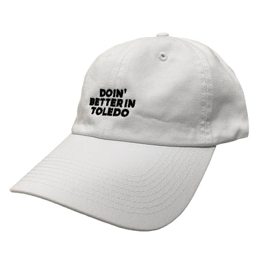"White baseball cap with ""Doin' Better in Toledo"" in black embroidery in center."