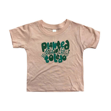 "Light pink short sleeved toddler size shirt with ""Planted in Toledo"" in teal and green on the center chest intertwined with teal and green leaves."