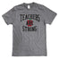 "Gray short sleeve t-shirt with imprint on center chest reading ""Teachers are Strong"" in black type with a white outline, with a red and green apple in the center."