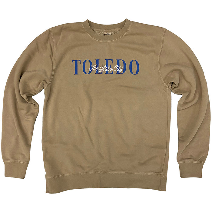 Sand colored sweatshirt with Toledo in blue ink with The Glass City embroidered overtop in cream thread.