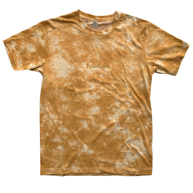 Gold and cream tie die shirt with small Toledoan type printed in center chest in dark gold ink in a serif font