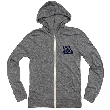 Long sleeved, zip-up hoodie in gray with cream colored zipper, small Toledo shadowed navy print on left chest reading TOLEDO in negative space.