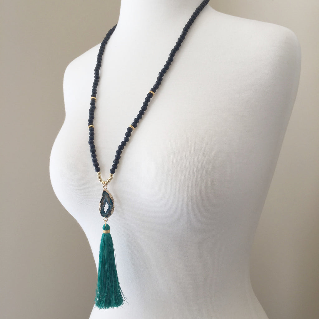 Muted matte black glass beads accented with a 14k gold edged druzy green pendant and a persian green tassel.