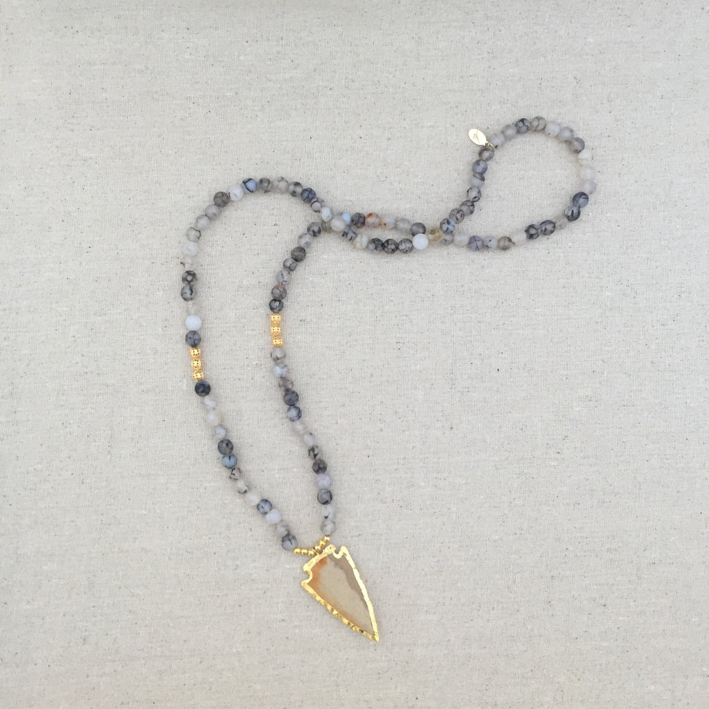 Black and white fire agate beads accented with gold and finished with a 24k gold edged earth toned jasper arrowhead.