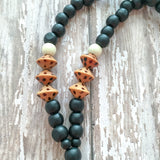 Black wooden beads accented with brown and gold, finished with grey natural cotton tassel.