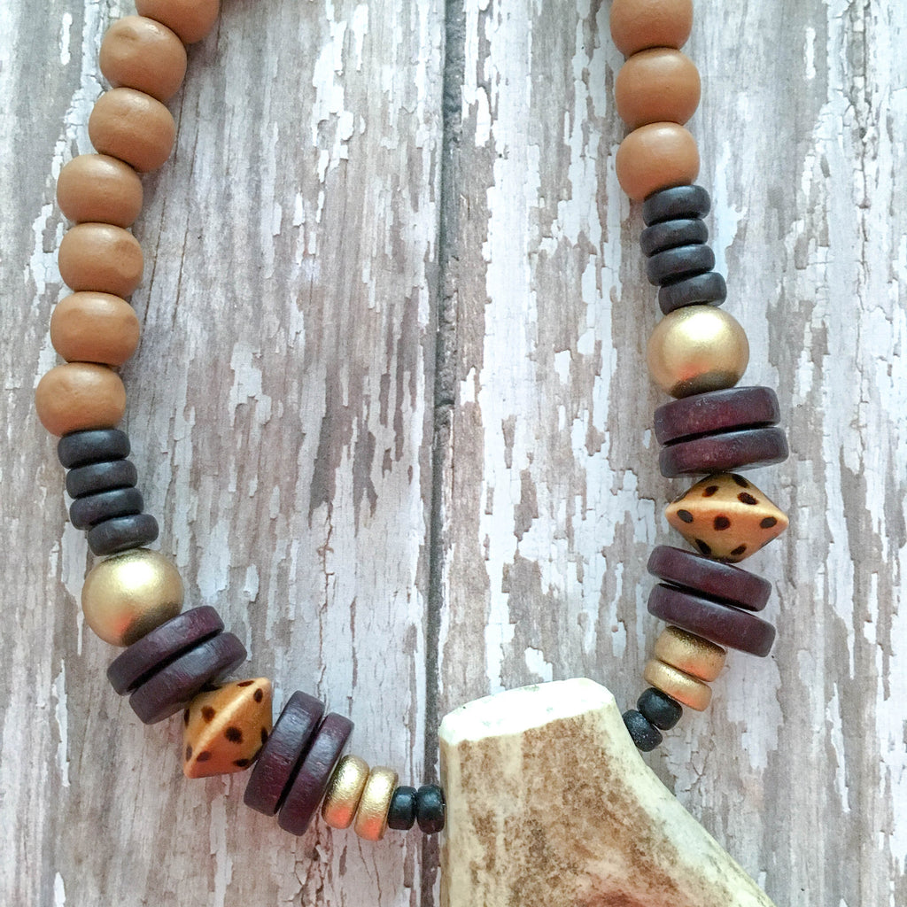 Caramel wooden beads accented with espresso and gold, finished with a naturally-shed forked deer antler.