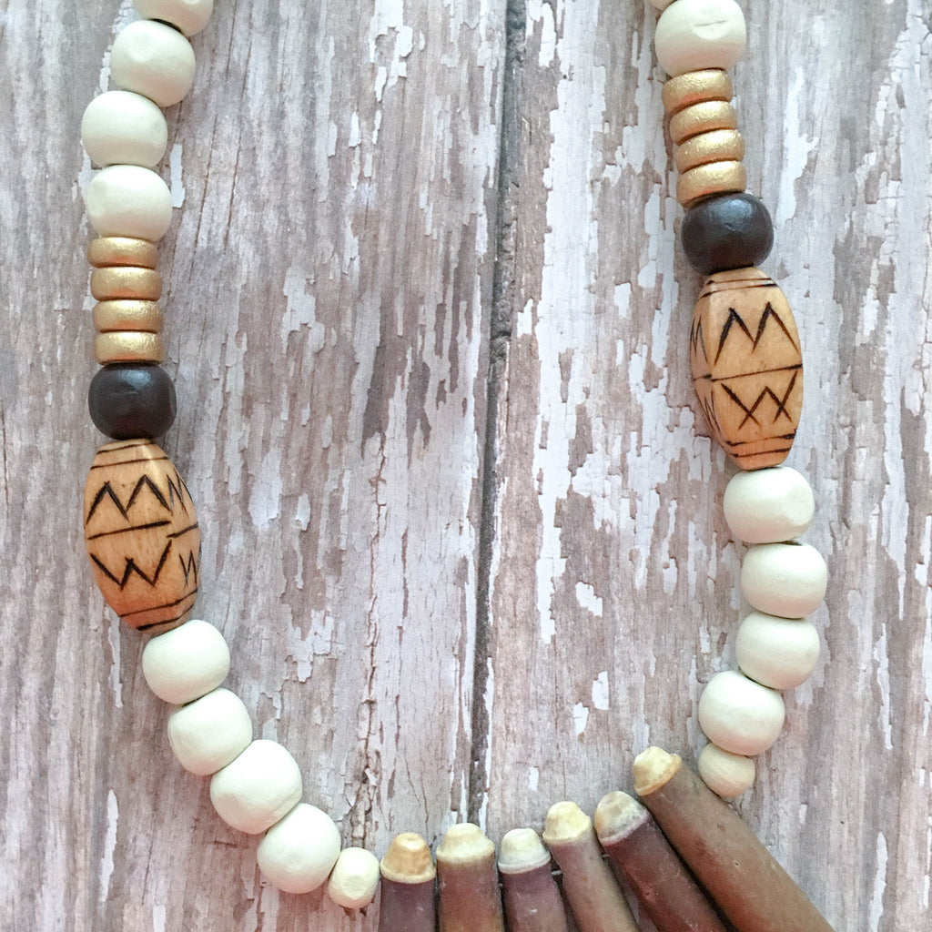 White wooden beads accented with gold and natural beads, finished with 6 natural sea urchin spine bones.