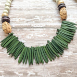 White wooden beads accented with wooden gold, brown, and manga-manga beads, finished with hunter green coconut spikes.