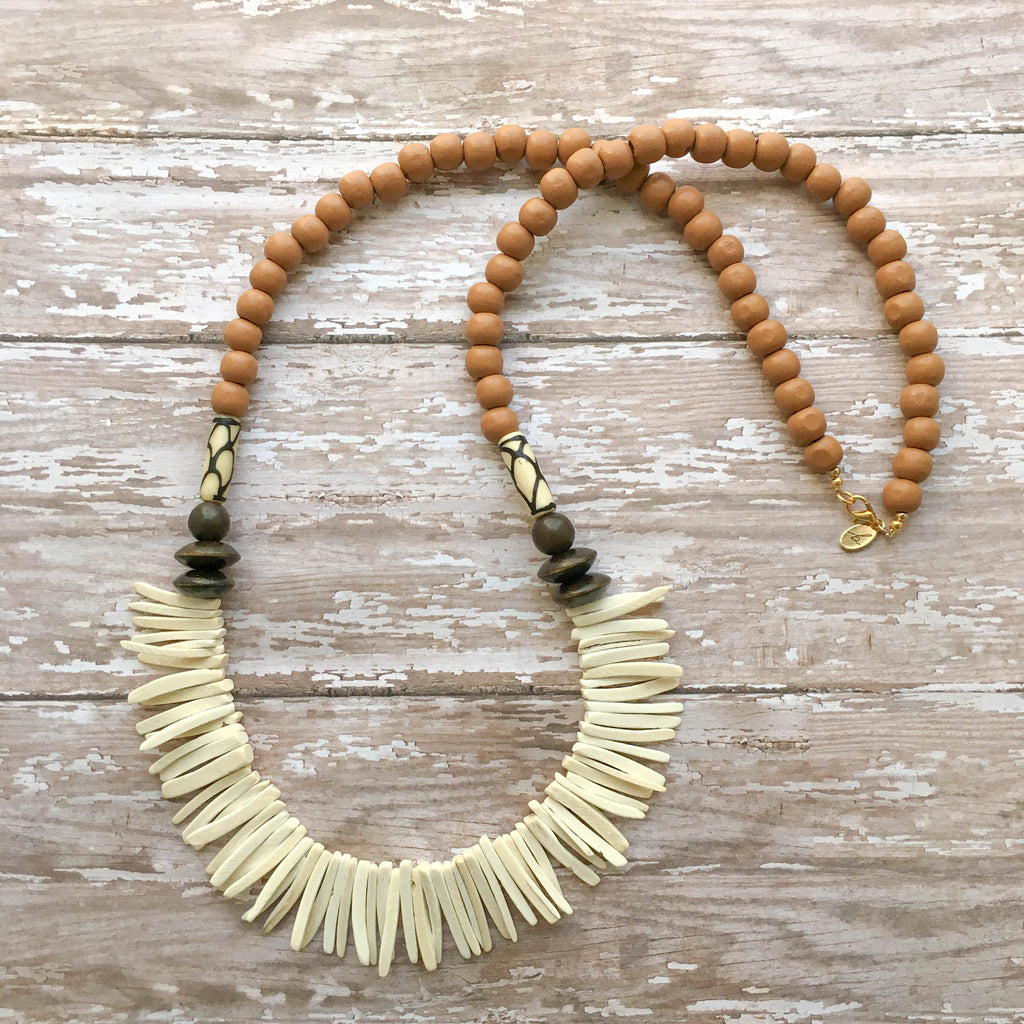 Caramel wooden beads accented with hand-painted white and black african beads and manga-manga beads, finished with cream spiked coconut beads.
