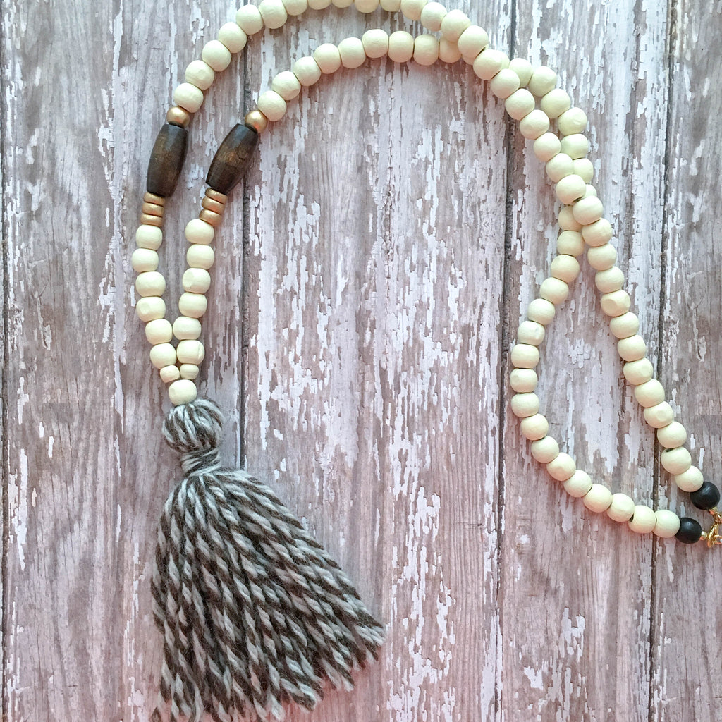 White wooden beads accented with brown and gold, finished with a brown and white natural cotton tassel.