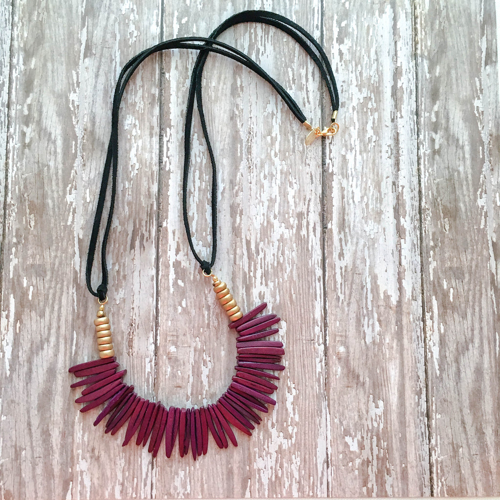 Black suede leather necklace accented with gold beads and finished with dark purple spiked coconut beads.