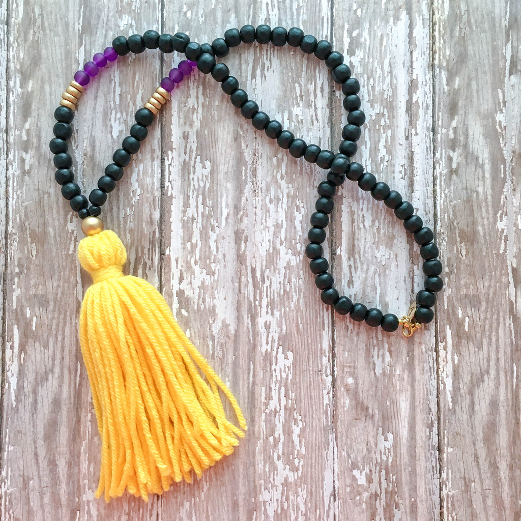 Black wooden beads accented purple beads and finished with a purple or yellow tassel.